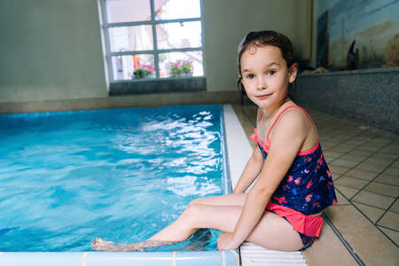 Portrait girl having fun in indoor swimming-pool. The girl is resting at the water park. Active happy kid. Swimming school for small children. Concept friendly family sport and summer vacation.