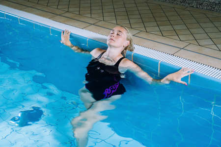 Beautiful young woman relaxing in indoor spa swimming pool. The girl is resting at hotel spa. Young woman relaxing in resort. Person enjoying jet of water in spa resort. Retreat and vacation Concept.