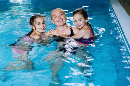 Mother with two daughters having fun in indoor swimming-pool. Girl is resting at the water park. Swimming school for small children. Concept friendly family sport summer vacation. Selective focus. Zdjęcie Seryjne