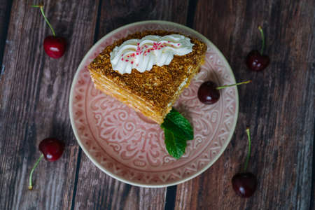 Piece of multilayer honey cake with cream. Classic honey cake pieces with custard. Homemade honey cake on wooden background with cherry and mint leaves. Delicious slice of layered tart on plate