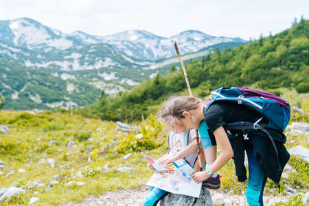 Children hiking on beautiful summer day in alps mountains Austria resting on rock. Kids look at map mountain peaks in valley. Active family vacation leisure with kids.Outdoor fun and healthy activity