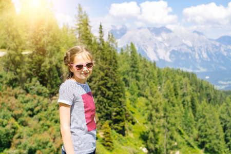 Girl hiking on beautiful summer day in alps mountains Austria, resting on rock and admire amazing view to mountain peaks. Active family vacation leisure with kids.Outdoor fun and healthy activity.