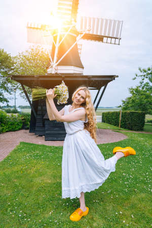 Woman dressed on traditional Dutch dress, wooden shoes yellow clogs klompen holding bouquet of Chamomile flowers with windmill on background. Retro vintage and countryside netherlands concept Standard-Bild
