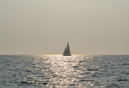 Calm sea and the lonely sailing boat on the glowing water in sunny day Stock Photo