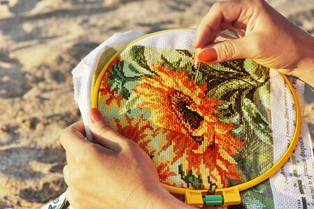 Woman hands making cross-stitch counted-thread embroidery Stock Photo