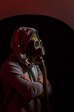 Human in gas mask in red light rays standing sideways on black background. Enviromental protection, radiation ans biohazard concept.