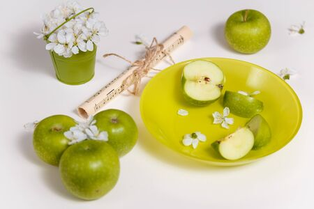 Green apples, note paper and cherry blossom on green plate standing on white table background. Copy space. Spring concept. 免版税图像