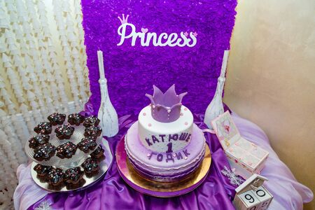 Girlish purple cake with crown and inscription - name Katusha is 1 year old. First birthday party. Candy bar with muffins and inscription Princess.