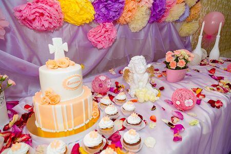 Baptism candy bar, angel statue, cupcakes, unfocused cake. Mastic cross on cake for christening child party. White candles and flower petals on the table.