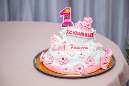 Girlish cake with pink mastic flowers and cnumber 1. One year old first birthday party. Inscription on candle My birthday. Inscription on cake - name Ksushenka is one year old.