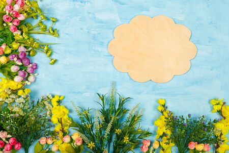 Artificial multicolored flowers and wooden cloud shaped template or mock up on blue painted wooden background. Spring blossom, Easter, women day, mothers day, 8 March concept. Copy space. Imagens