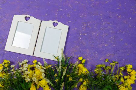 Artificial yellow flowers and empty white frame or mock up on purple painted wooden background. Spring blossom, Easter, women day, mothers day, 8 March concept. Copy space.