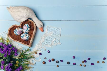Wooden heart shaped box with decorated Easter eggs. White lace, goose toy, purple flowers and beads on blue background. Easter and spring concept. Flatlay, place for text. Imagens