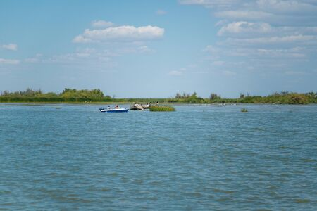 River and blue sky summer landscape with people sailing in boat