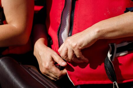 Female hands fasten up life jacket on motor boat. Lifeguarding by waterspor, vacation leisure equipment concept, close up.