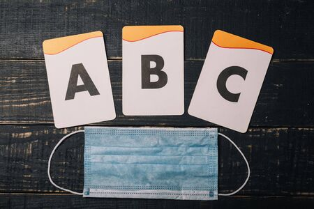 Alphabet letters cards and medical gauze mask on wooden table. Covid 2019, selfisolation, distant learning, home education, remote study concept.