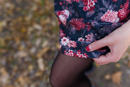 Female hand with red manicure holding dress or skirt with red flowers on blurry autumn background. Nature, health and beauty, hands and fingernails care concept. Imagens