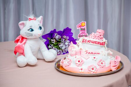 Girlish cake with pink mastic flowers and cnumber 1. One year old first birthday party. Inscription on candle My birthday. Inscription on cake - name Ksushenka is one year old. Cat toy on table.