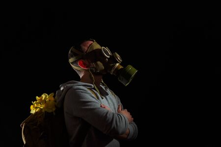 Man in gas mask with flowers in backpack. Enviromental pollution, nature protection, ecology disaster and hope concept. Black background, copy space.
