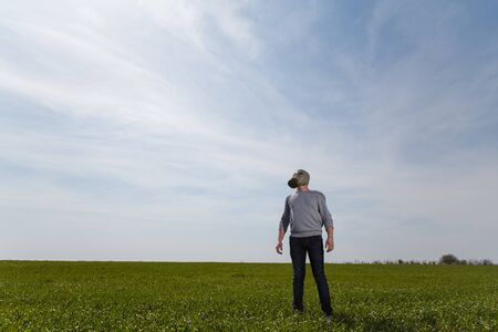 Man in gas mask standing in green field on clear blue sky background. Enviromental protection, ecology, Earth saving, pollution prevention and hope concept. Copy space.
