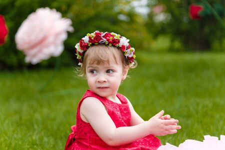 Little girl in red dress playing on the green lawn with high artificial rose flowers on background. Springtime, blossom and childhood concept.