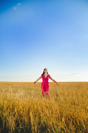 Girl in bright dress standing in golden wheat field on blue sky background.