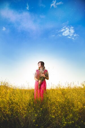 Girl in bright dress standing in golden wheat field on blue sky background and holding flowers bouquet.