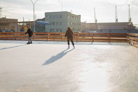 Two people skating on rink in skates. Winter sports, leisure, active way of life concept. Imagens - 148906269