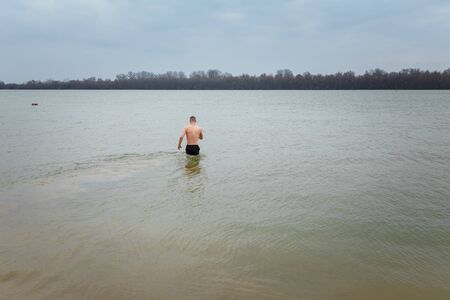Man standing in water. Christening or baptism bathing in winter river. January rite, religious tradition or ritual of God believers.
