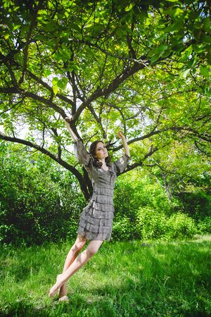 Pretty girl in dress touching the tree or holding branches with green leaves. Springtime and connection with nature concept.
