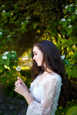 Beautiful teenager girl in white dress with long dark hair in apple garden holding dandelion flower. Spring blooming and youth concept.