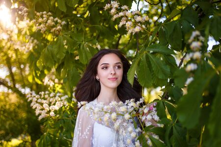 Beautiful teenager girl in white dress with long dark hair at blossoming chestnut tree. Spring blooming and youth concept.