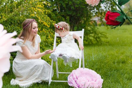 Little girl and mother in white dresses playing  on the green lawn with high artificial rose flowers on background. Springtime, blossom and childhood concept.