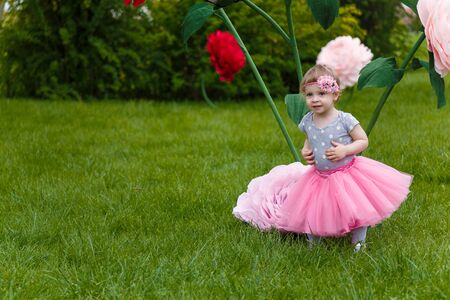 Little girl in pink fluffy tutu skirt playing  on the green lawn with high artificial rose flowers on background. Springtime, blossom and childhood concept.
