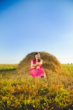 Girl in bright dress sitting in golden wheat field at a haystack on sunset and blue sky background. Rural scene, freedom and relaxation concept.