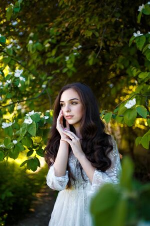 Beautiful teenager girl in white dress with long dark hair in apple garden. Spring blooming and youth concept.