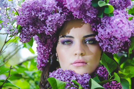 Close portrait of a beautiful girl with tender makeup and big lilac flowers wreath on head. Beauty headshot, spring blossom concept.