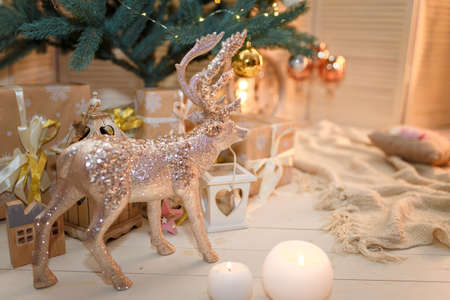 Merry Christmas and Happy New Year living room interior with decorated firtree, golden garland lights, white candles, reindeer toy and shiny champagne glasses. Winter holidays concept. Фото со стока