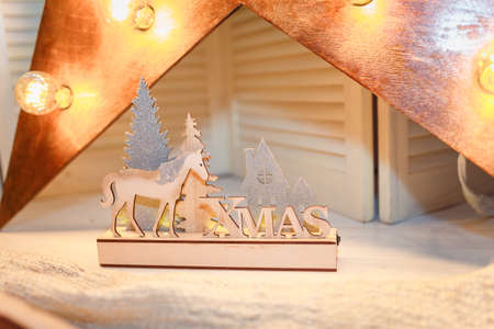 Merry Christmas, Happy New Year and Winter holidays concept. Golden garland lights, wooden decoration with silver firtree, house and horse.