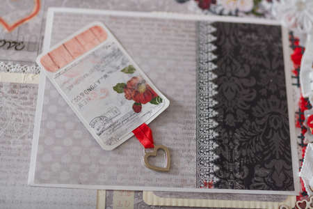 Soft focused close up shot of scrapbooking photo album page with paper decorative elements, flowers, metallic heart pendant, lace. Leisure and hobby concept.