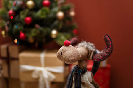 Izmail, Ukraine - December 2018. Editorial. Portrait of toy reindeer on the blurry decorated tree background. Merry Christmas, Happy New Year, winter holidays concept. Brown background, place for text Stock Photo