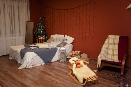 Modern bedroom interior with bed and cushions, toys and garland on the brown wall background. Merry Christmas, Happy New Year and winter holidays concept.