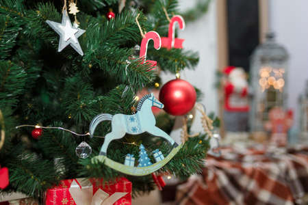 wooden rocking horse toy and decorations hanging on fir tree branches with santa claus and lantern lights on blurry background. Merry Christmas, Happy New Year and winter holidays concept. Reklamní fotografie
