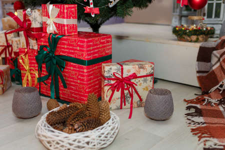 Merry Christmas and New Year wrapped present boxes standing under fir tree on white wooden floor. Wickerbasket with cones and gray candlesticks standing around. Winter holidays concept.