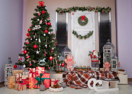 Christmas living room interior with fir tree, wreath, wrapped presents, wooden decorative sled, plaid, lanterns, red and silver bulbs, Santa Claus and gingerbread man toys. New year and winter concept Reklamní fotografie