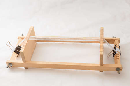 Wooden beadwork machine with strained white threads for making handmade jewelry, female bijouterie, hobby and leisure.