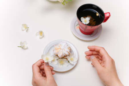 female hands, cup of jasmine tea, cake with sugar powder on plate on white table.