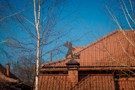 Soft focused shot og buildings roof with red tile on blue spring sky background with burch on foreground and weather vane shaped as a person with ladder and cat.