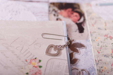 Soft focused close up shot of scrapbooking photo album page with paper decorative elements, flowers, metallic pendant heart. Leisure and hobby concept.