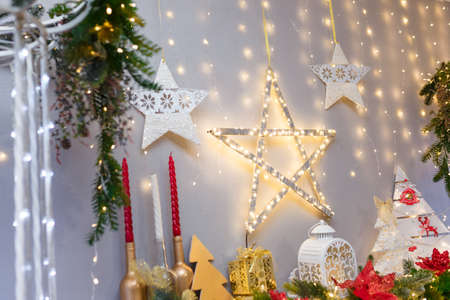 Merry Christmas, Happy New Year decorations with shiny stars, candles, white lantern, fir branches, bulbs, wooden toy hearts and warm garland lights over a fireplace or piano. Winter holiday concept.